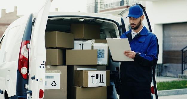 青い衣装の白人の格好良い配達員とクリップボードに文書を記入するカートンボックスと白いバンでキャップ。アウトドア。