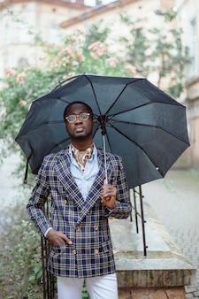 フォーマルな服を着た黒い傘の下で曇りの天候で市内中心部に立っているハンサムなアフリカ系アメリカ人実業家の都市の肖像。