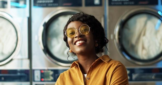 Закройте вверх красивой молодой афро-американской женщины в желтых солнечных очках жизнерадостно усмехаясь к камере в комнате прачечной. портрет довольно счастливая девушка смеется со стиральными машинами