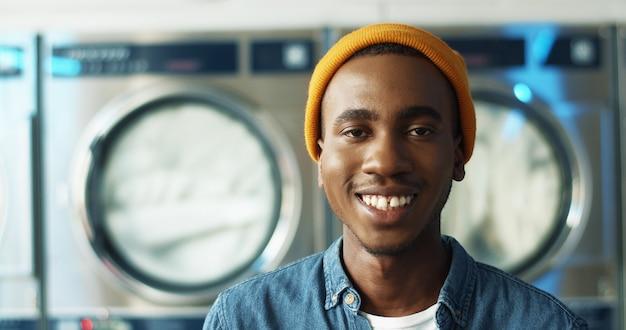 ランドリーサービスルームのカメラに笑顔の陽気な若いアフリカ系アメリカ人のクローズアップ。洗濯機で笑っているハンサムな幸せな男の肖像画。