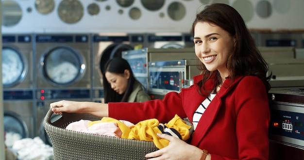 Портрет красивой кавказской стильной женщины усмехаясь к камере и держа корзину с пакостными одеждами пока стоящ в прачечной. красивая девушка смеется чистой одежды в стиральных машинах.