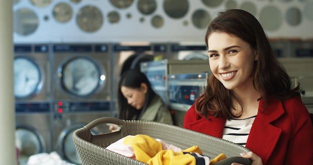 Съемка портрета молодой кавказской милой женщины усмехаясь к камере и держа корзину с пакостными одеждами пока стоящ в прачечной. красивая девушка с чистой одеждой в общественных прачечная