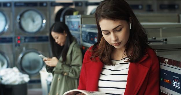Кавказская молодая красивая и стильная девушка, сидя в прачечной. журнал чтения красивой женщины и листать страницы пока ждущ одежды, котор нужно помыть в общественной прачечной самообслуживания.