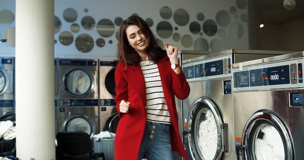 Кавказская радостная красивая и стильная женщина с удовольствием и танцами в прачечной, в то время как стиральная машина работает в общественной прачечной самообслуживания.