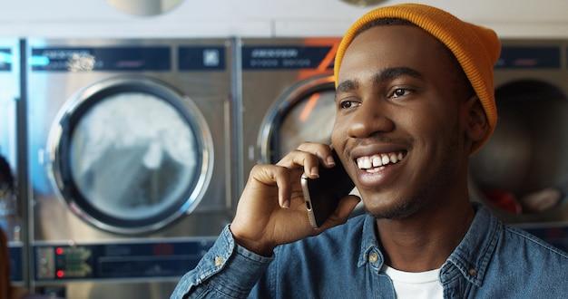 携帯電話で話しているとランドリーサービスルームで笑顔の黄色い帽子の若いアフリカ系アメリカ人陽気なハンサムな男のクローズアップ洗濯機で携帯電話で話す幸せな男。スマートフォン会話