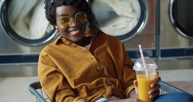 Милая и счастливая афро-американская девушка сидя в вагонетке и выпивая апельсиновый сок с соломой, отдыхая и ожидая одежды быть вымытым. стильная женщина, потягивая напиток в прачечной.