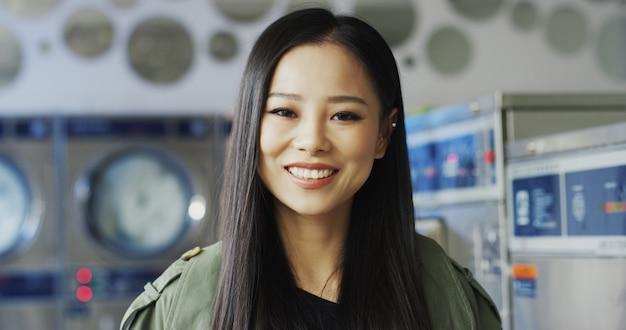 Закройте вверх красивой молодой азиатской стильной женщины усмехаясь радостно к камере в комнате прачечной. съемка портрета довольно счастливой девушки смеясь над с стиральными машинами в прачечной.