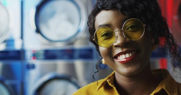 ランドリーサービスルームでカメラに元気よく笑顔の黄色いサングラスで美しい若いアフリカ系アメリカ人女性のクローズアップ。洗濯機で笑ってかなり幸せな少女の肖像画。