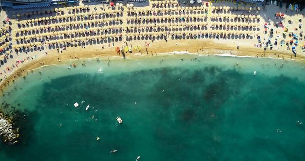 美しい澄んだ海の水で泳ぐ観光客と砂浜の空撮。上からの太陽が降り注ぐビーチの眺め。夏の時間-海、砂、パラソル、タオル、椅子、観光客、モーターボート、ヨット。
