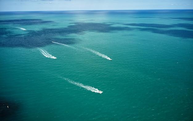 青い海でセーリング白いボートのドローンビュー。オープンウォーターのモーターボートの空撮。海と海の旅行と輸送。