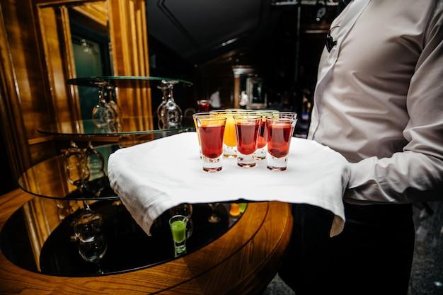 Красивая линия строки разноцветных алкогольных коктейлей на вечеринке украшенный столовый сервиз стол на мероприятии на открытом воздухе, фотография с красивым боке