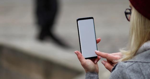 彼女の携帯電話にテキストメッセージを入力する実業家
