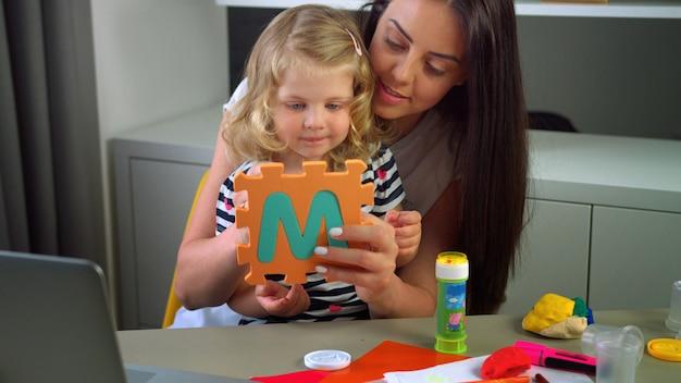 Кавказская женщина с длинными черными волосами и ее маленькая дочь со светлыми вьющимися волосами, ваяющие с пластилином на фоне живой. в помещении.
