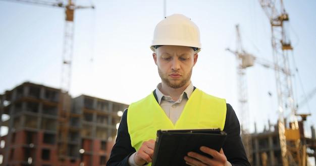 Инженер-строитель в белом шлеме и зеленом жилете на строительной площадке используя таблетку для работы. открытый.