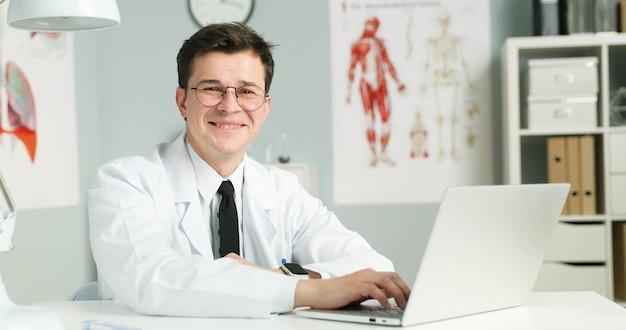 Молодой доктор сидит с ноутбуком в медицинском кабинете