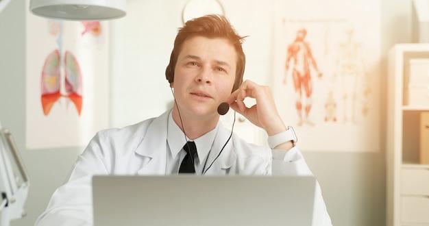 患者と話している彼女のラップトップの前にヘッドセットを持つハンサムな若い医者。
