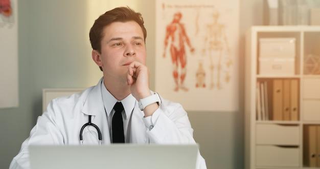 ハンサムな若い医者はラップトップを使用してオンライン相談を与える