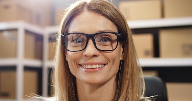郵便局の店の屋内のカメラに笑顔のメガネで金髪の女性の肖像画