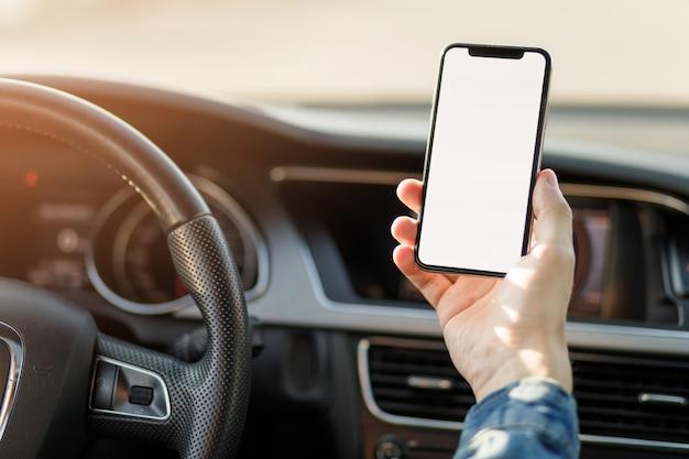 車の中で携帯電話を持つ若いビジネスマン。空白の画面を持つスマートフォンを抱きかかえた。