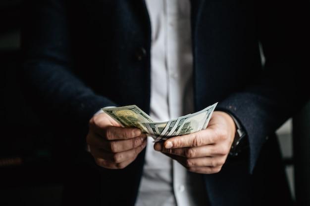 Человек считать деньги, человек в деловой одежде с долларами.