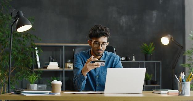 Арабский молодой мужской офисный работник в очках, сидя за столом, проведение кредитной карты и покупки в интернете на переносном компьютере.