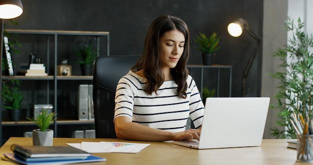 Молодой занятой женский работник офиса сидя на таблице, работая на портативном компьютере и рассматривая.