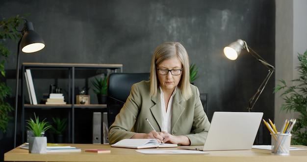 Старшая коммерсантка сидя в офисе и писать в примечаниях в тетради, работая на портативном компьютере и делая планирование бизнеса.