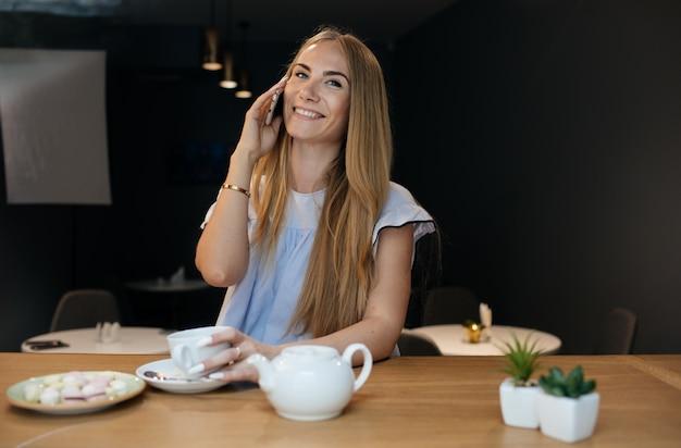 カフェに座っている若い女性」と電話で話す
