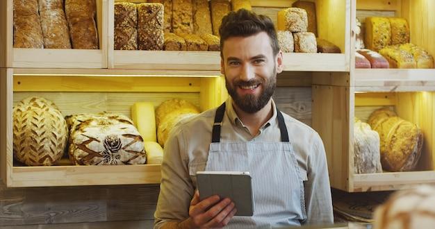 パン屋さんで働いて、デジタルタブレットコンピューターを使用して幸せなパン屋の肖像画。