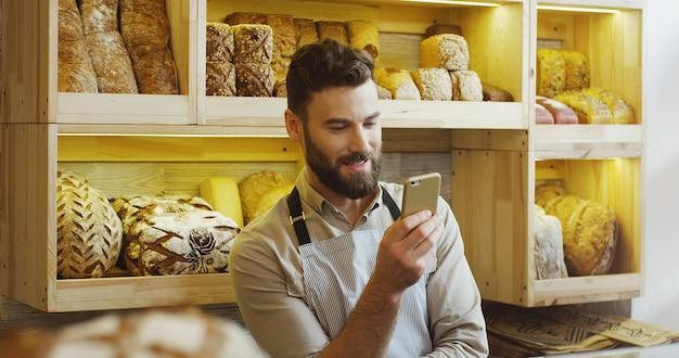 スマートフォンを使用してパン屋さんで働いて幸せなパン屋の肖像画。