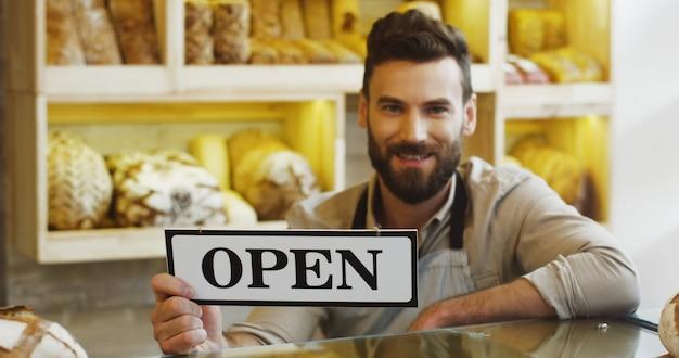 Портрет красивого усмехаясь хлебопека держа открытый шильдик в магазине хлебопекарни.