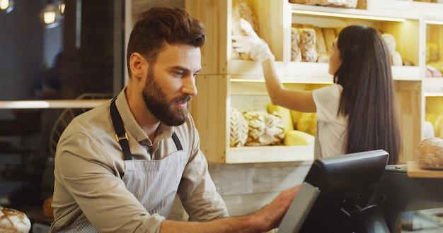 パン屋のカウンターでバイヤーにバゲットを販売する白人の若い男性と女性のパン屋のクローズアップ。屋内。