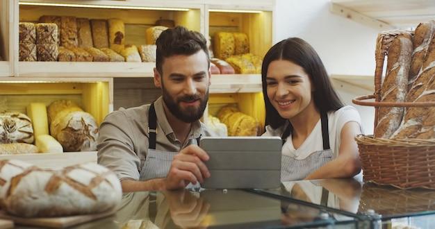 魅力的な男性と女性のパン屋がパン屋のカウンターに立っている間、タブレットデバイスで何かをスクロールして見ています。屋内