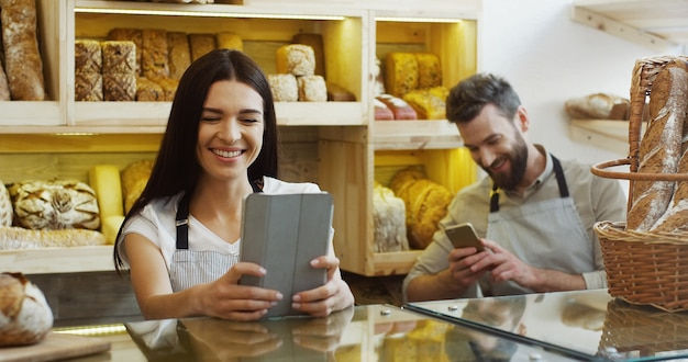 白人のきれいな女性の売り手がスクロールし、ベーカリーショップのカウンターに立っている間タブレットコンピューターをテーピング、男は彼女の後ろに電話で話しています。同僚が話したり笑ったりしている。屋内