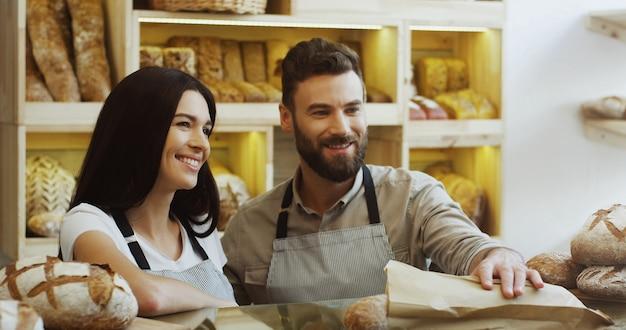 男性の同僚が手伝ってくれるバゲットを販売するパン屋の魅力的な女性の売り手。カウンターで。屋内で