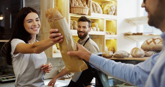 男性のハンサムな同僚が彼女を手伝っている間にパン屋の売り手がバゲットを男に売っている美しい女性。カウンターで。屋内