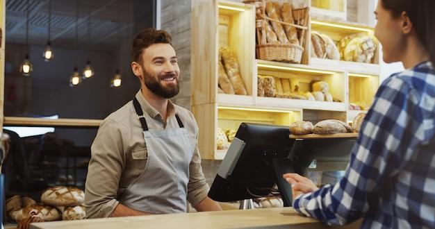 購入する前にパンを選ぶ若い美しい女性のバイヤーと話しているパンの店で白人の若い男の売り手。カウンターで。内部