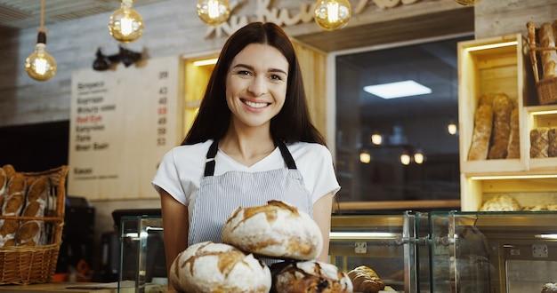 スクロールし、店のカウンターに立っている間タブレットコンピューターをテーピングのメガネのきれいな女性のパン屋。屋内