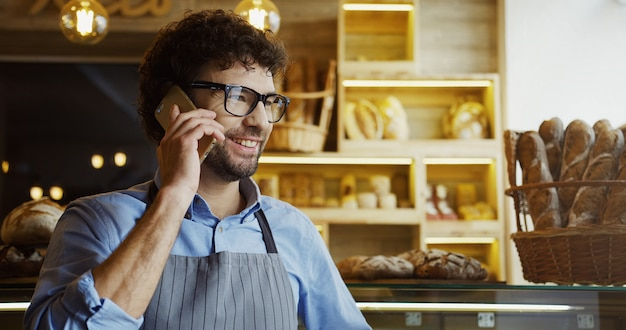 使用して、携帯電話で話しているベーカリーショップで働く幸せなパン屋の肖像画