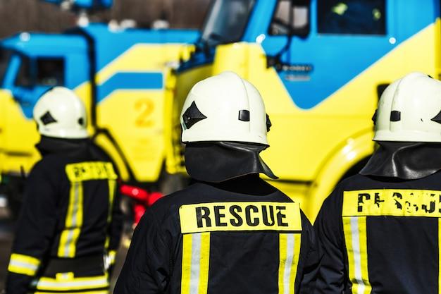 Группа пожарных в безопасном шлеме и форме стоя у машины