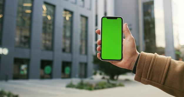 Обрезанный снимок вид мужской руки, держащей смартфон на фоне улицы города с пустой экран копией пространства для вашего текстового сообщения или информационного содержания