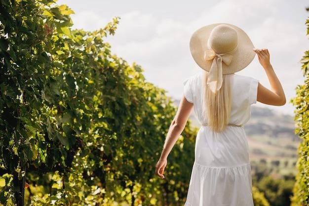 Красивая девушка в шляпе гуляя на большую плантацию виноградника, тоскану, италию.