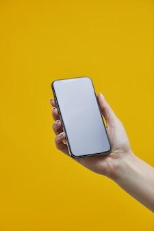 スマートフォンのモックアップ。黄色の背景に空白のディスプレイと黒の携帯電話を持っている女性の手