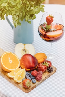 フルーツカクテルとベリーとミントの葉と白い木製のテーブルにスライスされたフルーツトレイ
