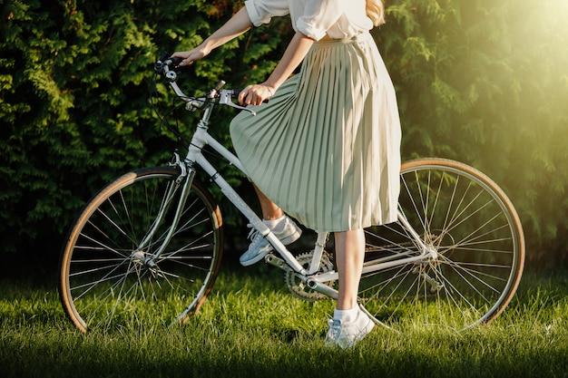 Молодая белокурая девочка с длинными волосами, стоящими около старинного белого велосипеда.