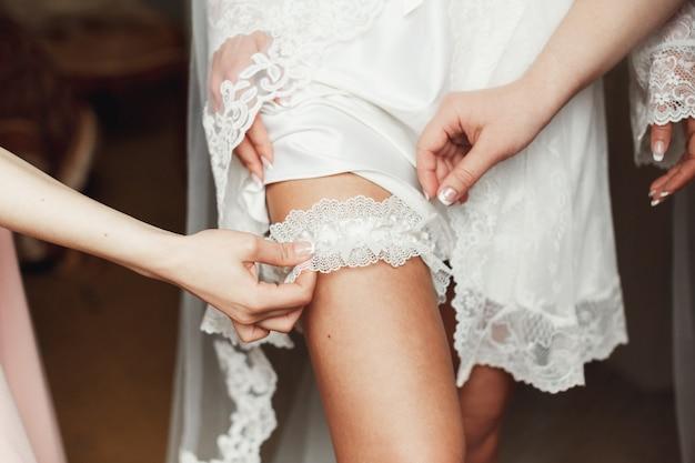 花嫁の脚にガーターを置く花嫁介添人