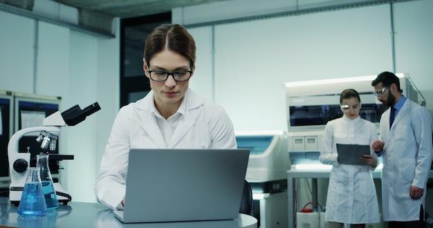 Портрет симпатичной кавказской женщины в очках и белом халате, проводящей исследование на портативном компьютере и анализ, глядя в микроскоп в лаборатории.