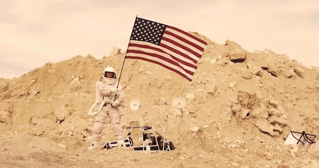 Астронавт с американским флагом, стоящий на скалистой горе чужой красной планеты / марса. первая пилотируемая миссия на марс