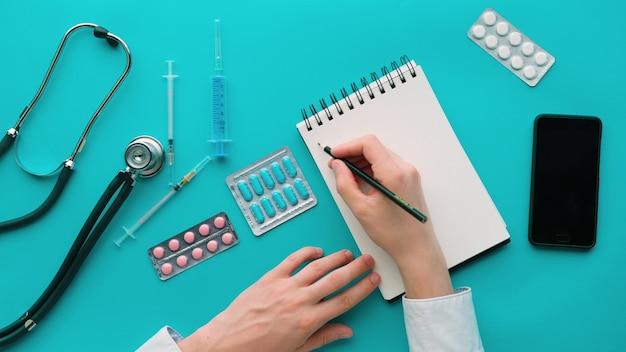 医学、医療、人々の概念。メモ帳、聴診器、薬、医師の机で注射器と医学の職場