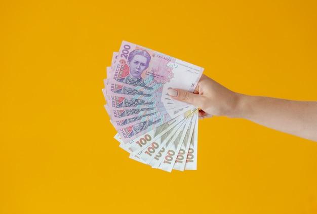 Крупным планом руки держат много денег. сто долларов банкнот и украинских гривен. фон бизнес концепции вид сверху с копией пространства